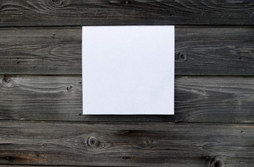 Blank sheet of paper on vintage wooden background. White paper with plenty of copy space. Blank paperwork template for design portfolios. Top view.
