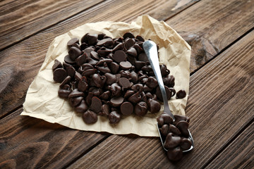 Tasty chocolate chips, parchment and spoon on wooden background