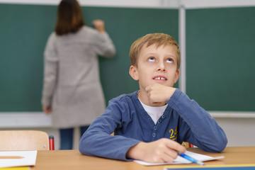 junge in der schule schaut nachdenklich nach oben