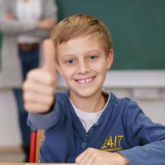 schüler in der grundschule zeigt daumen hoch und lacht