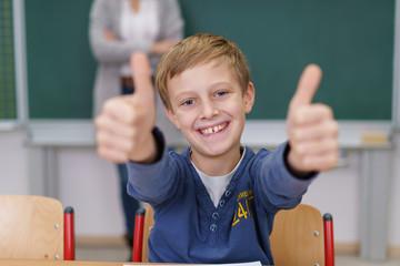glücklicher junge in der schule zeigt beide daumen hoch
