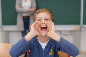 lachender junge sitzt in der schule und ruft laut