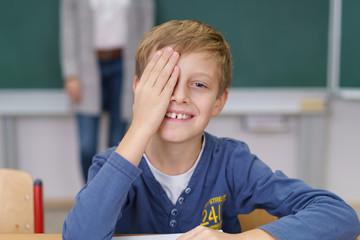 lächelnder junge in der schule hält ein auge zu