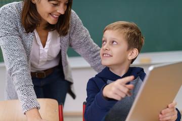 schüler zeigt seiner lehrerin etwas am tablet