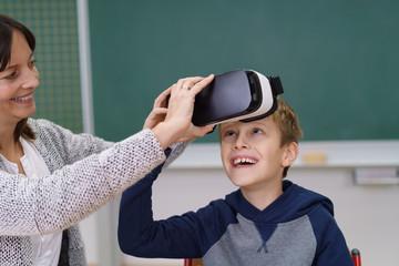 lehrerin setzt einem schüle ein virtual reality brille auf