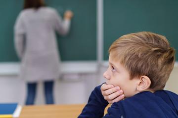junge in der schule schaut nachdenklich zur seite