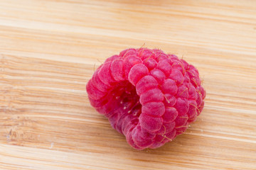 Ripe sweet raspberries on wooden table.
