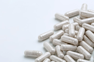 Heap of white capsules medications on white background. Copy space. High resolution product. Health care concept