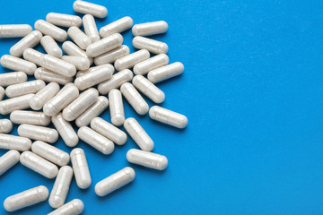 Many white capsules on blue background. Top view. High resolution product. Health care concept