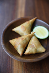 Baked samosa in wooden bowl