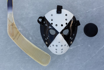 hockey stick, goalie mask and the puck on the ice