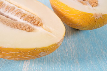 Cut fresh melon with seeds on a wooden background.
