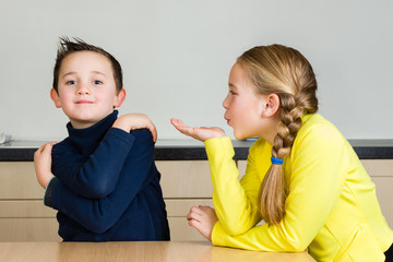 Child (girl) blows hand kiss to brother