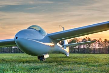 Segelflugzeug auf grüner Wiese im Abendlicht