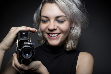 Female actor posing with a vintage camera as an artistic director, creative cinematographer or filmmaker.  She is advertising the Hollywood movie industry or film art schools.