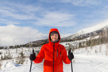 smiling man with ski sticks in winter mountains wearing red jack