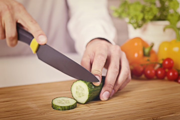 Chef's hands. Man is ready to prepare fresh salad. Chopping cucumber.