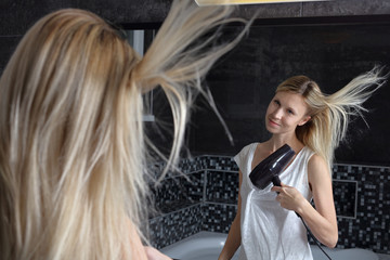 Portrait of Beautiful Smiling Woman Drying Healthy Long Straight Hair Using Hairdryer.