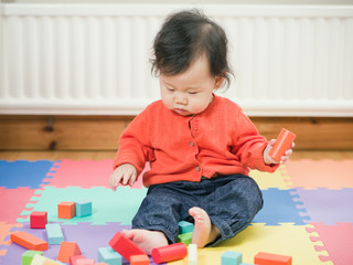 Asian baby playing building blocks