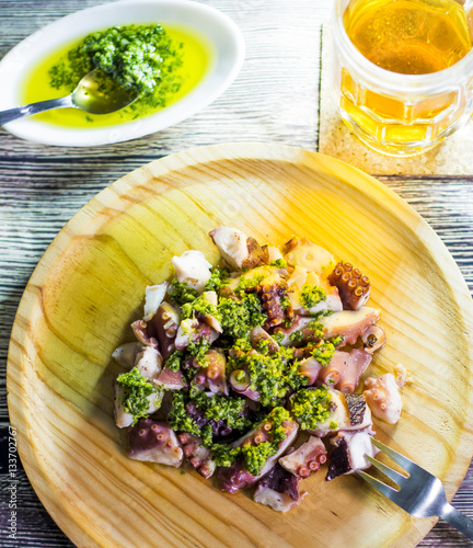 Foto: Octopus with paprika, a pitcher of beer and sauce on a wooden ta