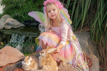 little fairy girl with rabbits in rock garden