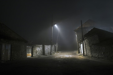 Night street country road with buildings and fences covered in fog lamp . Or Mysterious night in the centre of Ilisu village Gakh, Azerbaijan