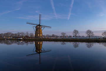 "Windmill ""the Googermolen"" with reflection in the water on the Ringvaart canal in Nieuwe Wetering the Netherlands."