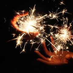 Close up of hands holding sparklers, Indianapolis, Indiana, USA