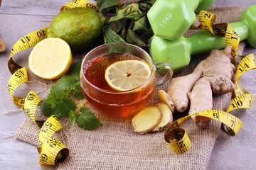 ginger tea - fitness liefestyle concept with tea, dumbells and measure tape - Healthy  tea detox