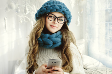 Close up portrait of young beautiful happy smiling girl using her smartphone. Lady looking at camera. Model wearing eyeglasses, blue big loop knitted hat and scarf. Day light, white room as background