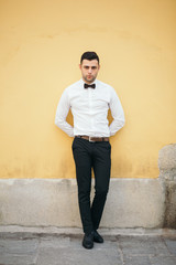 Welldressed Businessman Leaning On Yellow Wall