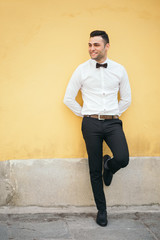 Happy Welldressed Businessman Leaning On Yellow Wall