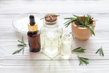 organic cosmetics with extracts of herbs rosemary on wooden background
