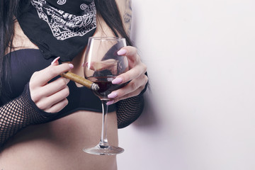 Woman wearing black jeans, a bra and a bandana, with a glass of red wine and a cigar, over a white background. No face, focus on the glass.