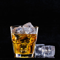 Glass of scotch whiskey and ice over black background.