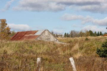 Old Barn parially hidden in the dip of an autumn field