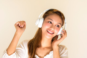 young woman listening music with wireless headphone, half latina and half asian