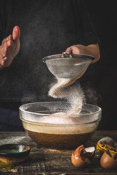Man sifting flour into bowl