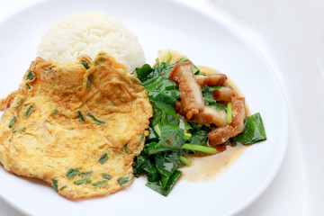 Stir fried kale with crispy pork and Thai Omelette with rice in white dish iIsolated on white background, Thai Food