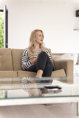 woman sitting on sofa with mobile phone