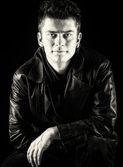 Handsome guy sitting in a leather jacket on a black background