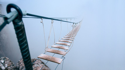 A rope bridge disappearing into fog.