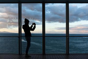 Woman taking photo at sunset