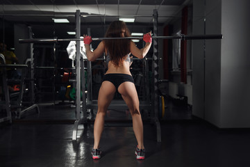 Young strong woman doing squats at the gym in front of a mirror with a barbell on her back.