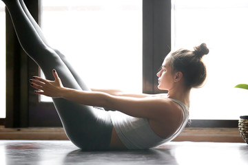 Young attractive woman practicing yoga, stretching in Paripurna Navasana pose, working out, wearing sportswear, grey pants, bra, indoor, home interior background, near the floor window