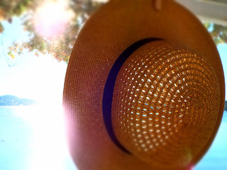 woman's straw hat hanging in front of cottage porch screen with sun beams and blurred lake in background