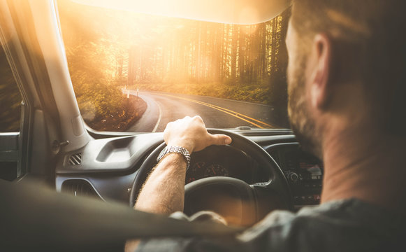 Mann fährt mit Auto durch einen Wald (Rückansicht) mit Gegenlicht