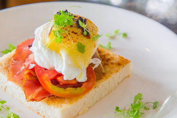 Fried egg with bacon and tomato on toast