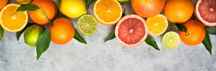 Citrus fruit on grey concrete table. Food background. Healthy eating. Long banner format good for web.