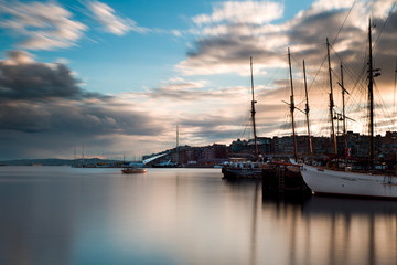 Oslo harbour at sunset. From Rådhusbrygga til Tjuvholmen. Long exposure